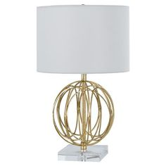 The Mills Lamp lends intriguing illumination. Set atop a square acrylic base, a golden orbital sculpture adds organic interest. The woven architecture and metallic finish add visual texture and modern appeal. Completing the airy contemporary look is a white drum shade.