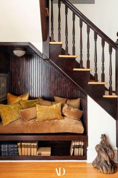 A cozy nook makes for the perfect perch underneath an interior staircase. #stairs #staircase #nook #cozy #pillows #velvet #wood #colonial #design #chair #bench Outdoor Swimming Pool, Swimming Pools, Office Nook, Fancy Houses, Cozy Nook, Pool Houses, Ping Pong Table, Architectural Digest, Glass Garage Door