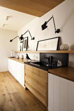 Nowoczesna biała kuchnia z czarnymi dodatkami i drewnianym blatem