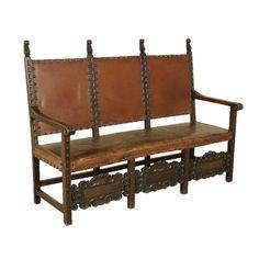 Divano tre posti riccamente intagliato. Seduta e schienale imbottiti, rivestimento in pelle con borchie.