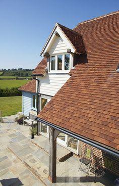 Handmade clay plain tiles to veranda roof with oak framed dormer.