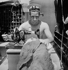 Credit: Cecil Beaton/Imperial War Museum  A sailor on board HMS Alcantara uses a portable sewing machine to repair a signal flag during a vo...