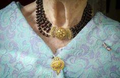 """""""Ik vind de Scheveningse dracht gewoon mooi"""" -  Halsketting en gouden broche. Beeld Niek Stam"""