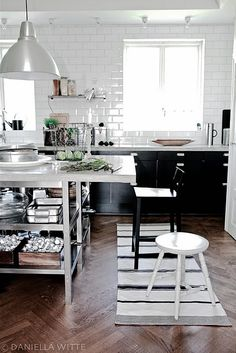 white subway tile with black cabinets. Stainless island. Herringbone wood floors.