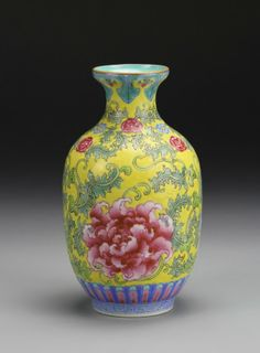 Chinese Famille Rose Enameled Vase painted with flowering scrolls on a yellow enameled ground, Kangxi mark on base. Height 6 in.