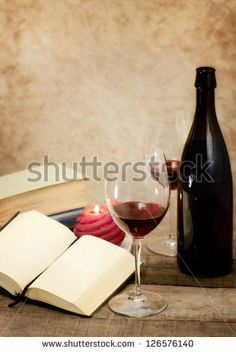 red wine glass with vintage books in romantic atmosphere