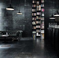 black, black, black! love this interior. black lounge, black bookshelf, black hanging lights black walls.
