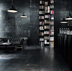 black, black, black! love this interior. black lounge, black bookshelf, black hanging lights black walls.