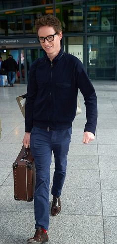 Eddie Redmayne is back in London, sporting specs and jazzy red socks. Shots at Heathrow Feb. 4, 2015.