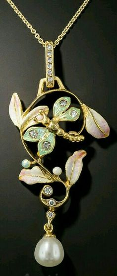 Art Nouveau Style Enamel Pendant. Graduated tones of pastel enamels adorn this curvilinear, 18K yellow gold pendant depicting a diamond studded pastel blue green dragonfly lighting on delicate pastel two-toned mauuve leaves within a whip-lashing stem sparkling with diamonds with a dangling pear shaped lustrous freash water pearl. This Art Nouveau style necklace measures 2 inches in length, including it's gracefully attenuated diamond set bail, and 15/16 inch in width. A contemporary 14K…