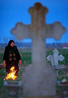 A woman stands at the grave of a relative after bringing incense and flowers during Orthodox Palm Sunday in Heresti cemetery, near Bucharest, April 8. Palm Sunday commemorates Jesus Christ's triumphant entry into Jerusalem, a week before his crucifixion. Romania's Christian Orthodox majority will celebrate Easter on April 15, a week after the Catholic believers.