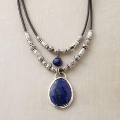 """TWOFOLD LAPIS NECKLACE - Thai silver beads line up along the lengths of leather cord that ground our double lapis pendant necklace, a lapis gem dangling from each. Sterling silver gem settings and toggle clasp. Gem color and shape may vary. Handmade. Exclusive. Approx. 17""""L."""