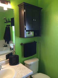 Lime green bathroom with black accents - added dark cabinet above the toilet and towel rack.