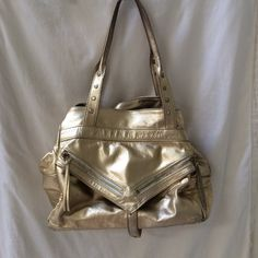 Gold Botkier Trigger purse Gold Botkier Trigger bag. Super cute and functional!! Worn by tons of celebrities!! Center zip-up section and two open side sections. Interior side zippered pocket. Bag is used but lining has no ink stains. Guaranteed authentic. Botkier Bags