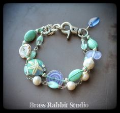 """Mixed media bracelet with lampwork sea star focal by Genea, lampwork swirl disks by Sue Beads, freshwater pearls, vintage and new Czech glass, lampwork wingding by Genea, faceted ceramic round by Bohully, large silver lobster clasp and nodical silver chain with a handmade seaglass charm. Adjustable, fits a 6.5"""" -8"""" wrist."""
