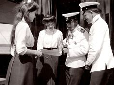 A beautiful photo, shot on the imperial yacht of Nicolas II. Tsar surrounded by an officer and his young sister Olga, looks a picture with them, holding by one of his daughters, probably made by her. I think it's Olga !