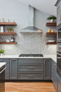 This brushed, stainless steel mosaic tile kitchen backsplash lends a more modern look to this transitional gray and walnut kitchen design.