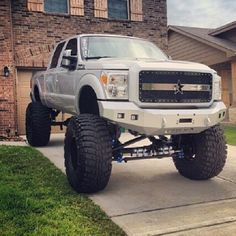 white Ford lifted truck oversize tires