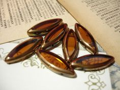 10 Large Amber Brown Gold Edged Dagger Oblong Glass Beads - $3 start bid in the Supplies with a Surprise LIVE Tophatter.com auction. Come get some deals in this fun auction with real time bids, and a FREE surprise with every item purchased.
