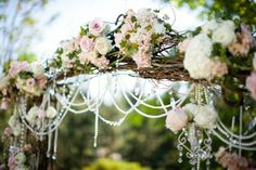 Wedding arch richly decorated with roses and garlands of pearls