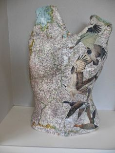Plaster torso decorated with map and birds
