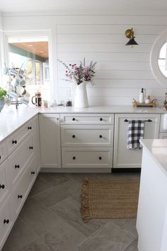 A really warm, inviting white kitchen with unique black cabinet hardware, wood plank on walls and love that tile on the floor!
