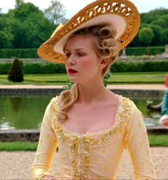 Kirsten Dunst as Marie Antoinette, on a beautiful yellow dress, with matching hat.