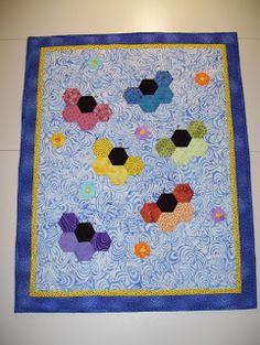 "Peggy made this cute quilt using the 1"" hexagons in Collection # 1, and the applique flowers were made with the 0.25"" hexagon collection."