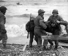 Unidentified survivors from a sunken LCVP (landing craft, vehicle, personnel, also known as a Higgins boat) are helped ashore at Omaha Beach during the invasion of Normandy, Normandy, France, June 6, 1944.