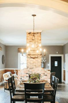 Chip uncovered layers of materials on the fireplace and took out both walls to open up the living and dining, leaving only the natural brick fireplace exposed. This fireplace is now the focal point of this house- it's a piece of history right in the middle of their living room