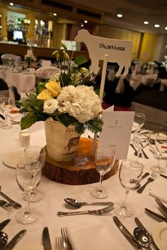 Farm wedding centrepiece. Tree slice, wooden cow with table name written on in calligraphy, milk bucket filled with flowers.