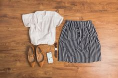 This look was created using Outfits by Cladwell. A closet view: White top. (responsibly-made option) Striped skirt (responsibly-made option) Flats (pointy toe flats, ankle strap flats). Watch.