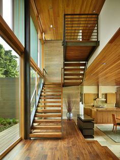Architect John DeForest. The open stairs in the two-story entry hall are anchored to a board-formed concrete wall and lead to the home's waterfront-facing bedrooms. Ceilings are fir.
