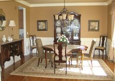 These homeowners liked their furniture, and since it was in good condition, there was no reason to replace it. The earth-toned rug we chose and warm colored paint we used on the walls and ceiling set the stage for this inviting room. The crown molding on the ceiling and the picture box molding and chair rail on the lower half of the walls provided just the right decorative detail. A new oil-rubbed bronze chandelier along with a few well placed accessories was the perfect finish.