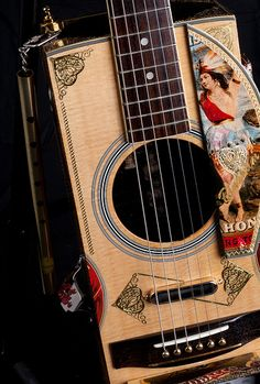 Cigar box guitar made with an acoustic guitar top.