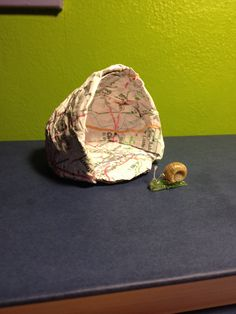 DIY mini snail and snail house. Made of: paper, cardboard, hot glue, glitter, wire, and a small snail shell. A great pet that could be used as a gift!