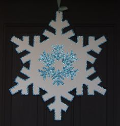 Large wooden snowflake that was painted white and glittered aqua.