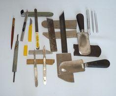 Matériel de reliure (flatlay) : couteau à pare rond, couteau à parer pointu, pointe, pointe fine, scalpels (n°3 et n°4), porte-plumes pour vaccinostyles, cutter (30°) et lames, manches pour lames de cutter et fers à rabots.