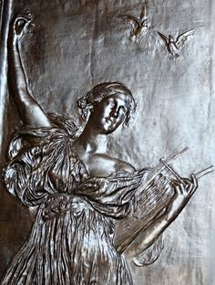 Detail of one of the three sets of bronze doors  created by Daniel Chester The allegorical figure, modeled in low relief, represents Music.