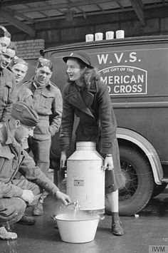 After tea, a group of Royal Engineers help Patience 'Boo' Brand fill up the washing up bowl with hot water from the water urn.