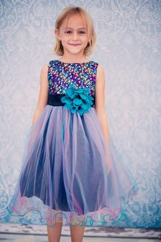 Blue Multi Sequin Holiday Party DressMulti Colored Sequin Tulle Party Dress This blue sparkle dress is new for the winter holidays. The blue dress has a blue satin base with fuchsia and yellow tulle mesh layers with matching sequin beads in matching colors acros the bodice. This dress is available inm atching baby sizes in both the blue and red dresses.