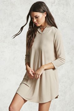 A cozy knit mini dress featuring a hood, 3/4 sleeves with dropped shoulders and a boxy silhouette.