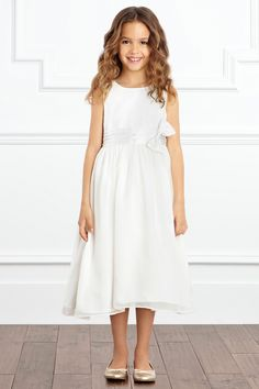 A gorgeous flower girl dress that exudes grace. The Lily Dress features a pretty ruched waistband detail with softly structured bow for a touch of elegance. The skirt is double lined with a tulle petticoat which creates a full silhouette. This is a unique and adorable choice for any little bridesmaid to be!