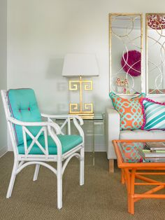 Coastal-style furniture and vibrant textiles lay the foundation for this white living room. Metallic accents paired with a sleek acrylic end table break up the primary hues. Interior, Tropical Living Room, Living Room Decor, Orange Home Decor, Home Decor, Teal Home Decor, House Interior, Interior Design, Coastal Style Furniture