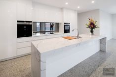 Polished concrete floor with white kitchen