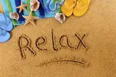 Picture of The word Relax written on a sandy beach, with scuba mask, beach towel, starfish and flip flops stock photo, images and stock photography.