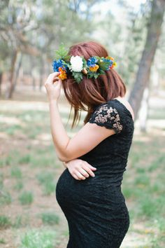 Maternity shoot with a flower crown, black lace, medium length hair and blue pointed flats.