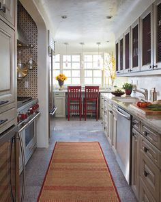 The bright rug running down this narrow kitchen makes it seem just a little less drab and cramped...