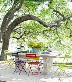Austin Back Patio: On this Texas ranch, metal folding chairs (from Barton Springs Nursery in Austin) offer colorful contrast to a simple stone table and patio built out of Texas limestone.