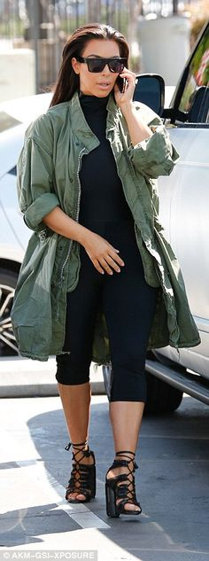 Military-inspired: The mother-of-two wore a long, army green jacket with cropped black leggings